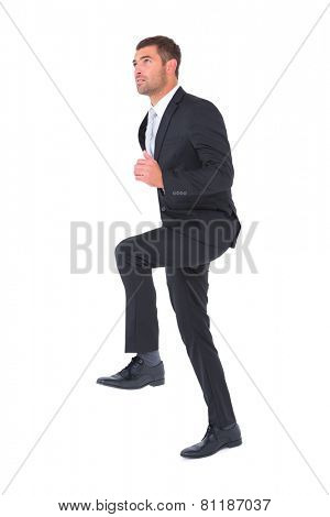 Businessman walking with his leg up on white background