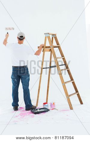 Full length rear view of man painting by step ladder on white background