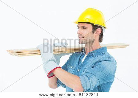 Handsome carpenter carrying wooden planks over white background