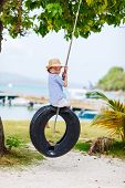 image of tire swing  - Adorable little girl having fun on tire swing on summer day - JPG
