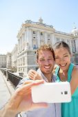 picture of two women taking cell phone  - Couple taking selfie photo on smartphone in Madrid - JPG