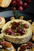 pic of brie cheese  - Brie cheese baked with nuts and grapes tasty and crispy baguette and bio herbs reduction of sugar nuts and balsamic vinegar - JPG