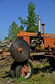 pic of osha  - An old antique tractor is equipped with with a huge pulley driven circular saw to cut loges into into firewood - JPG