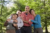 stock photo of pre-teen boy  - Portrait of Hispanic father and two boys outdoors in outdoor park - JPG