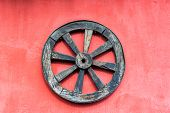 picture of wagon wheel  - Old wagon wheel and a red wall near Cotopaxi Volcano in Ecuador - JPG