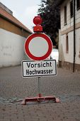 stock photo of flood-lights  - German sign that means passage forbidden with additional sign that says caution flood - JPG