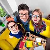 stock photo of nerd  - Three funny nerds looking together at camera standing in the room with couch and different digital stuff on background - JPG