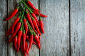 stock photo of chili peppers  - bunch of red hot chili peppers on a wooden rustic background - JPG