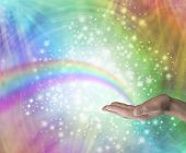 image of glitter sparkle  - Male hand palm up with a rainbow appearing to end in his palm on a rainbow colored background with glittering sparkles and swirling energy - JPG