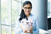 picture of holding money  - Closeup portrait happy smiling business woman holding pink piggy bank wearing big black glasses isolated indoors office background - JPG