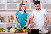 foto of heterosexual couple  - Happy young couple cooking together in the kitchen - JPG