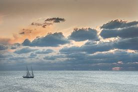 foto of under sea  - Small beautiful sailboat drifts in a calm sea under beautiful clouds - JPG