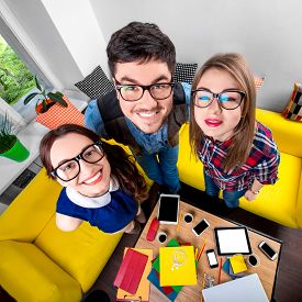 picture of nerd glasses  - Three funny nerds looking together at camera standing in the room with couch and different digital stuff on background - JPG