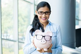 image of budget  - Closeup portrait happy smiling business woman holding pink piggy bank wearing big black glasses isolated indoors office background - JPG