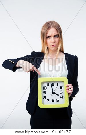 Angry businesswoman pointing finger on big clock over gray background and looking at camera