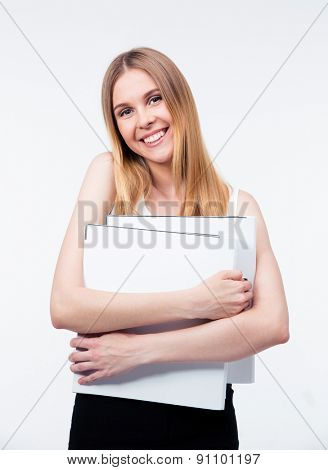 Cheerful young business woman holding folders isolated on a gray background. Looking at camera
