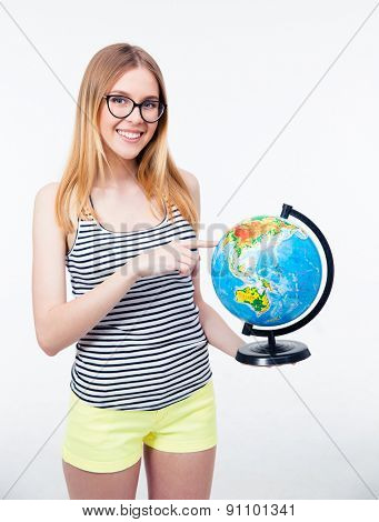 Happy young girl in glasses pointing finger on world globe over gray background. Looking at camera