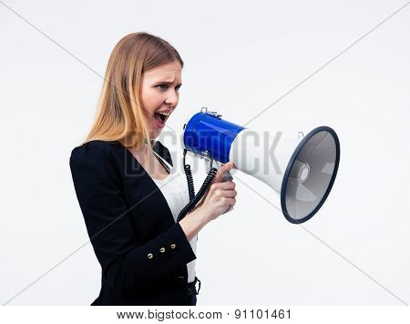 Young businesswoman screaming in megaphone over gray background
