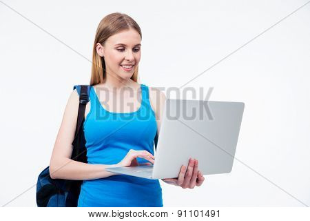 Smiling casual woman using laptop over gray background