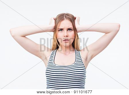 Woman with headache holding her hand to the head over gray background and looking at camera