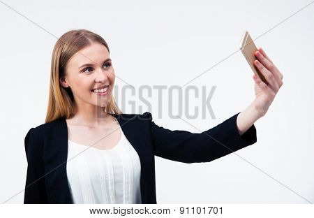 Happy young businesswoman making selfie photo on smartphone over gray background