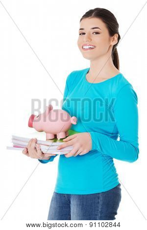 Happy woman standing with piggybank and notebooks.