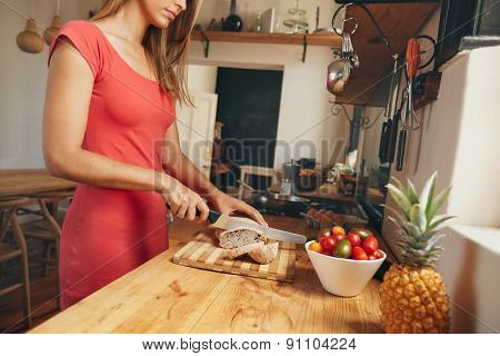 Young Woman Slicing A Loaf Of Bread In Kitchen