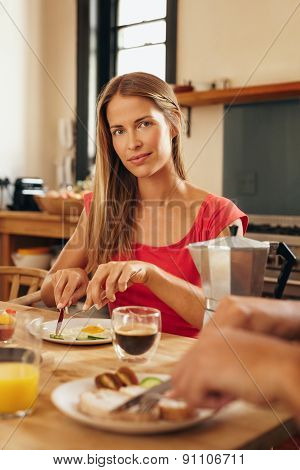 Young Woman Having Breakfast In Kitchen At Home