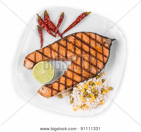 Grilled salmon steak with vegetables on plate.