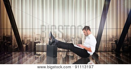 Businessman with feet up on briefcase against room with large window looking on city