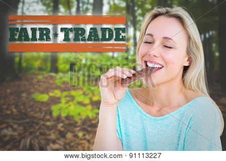 Pretty blonde enjoying and eating bar of chocolate against young plant against tree trunks in forest