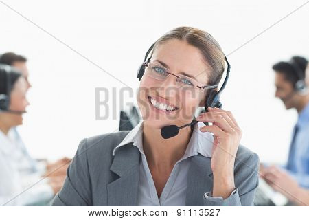 Smiling businessman with headsets looking at camera in office