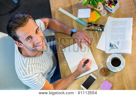 Smiling casual businessman writing in notepad in the office