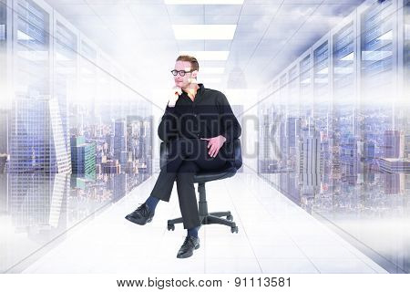 Thoughtful businessman sitting on a swivel chair against server room with towers