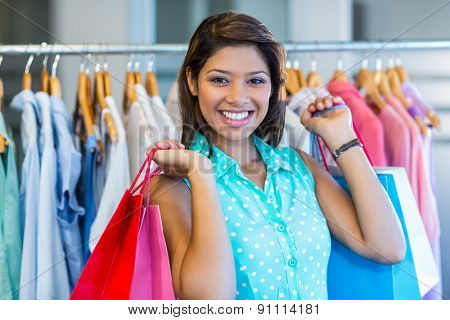 Beautiful brunette holding shopping bags in clothes store
