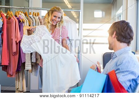 Happy blonde woman doing shopping with her boyfriend in clothes store