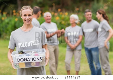 Happy volunteer holding donation box on a sunny day