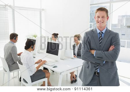 Smiling manager standing arms crossed with staff behind in call center