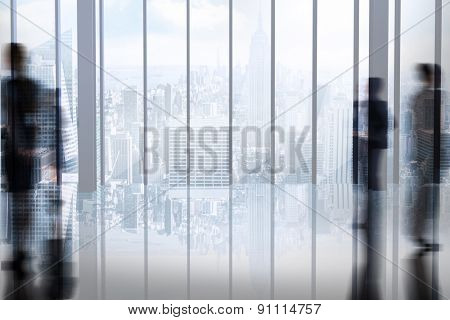 Silhouettes of business people against room with large window looking on city
