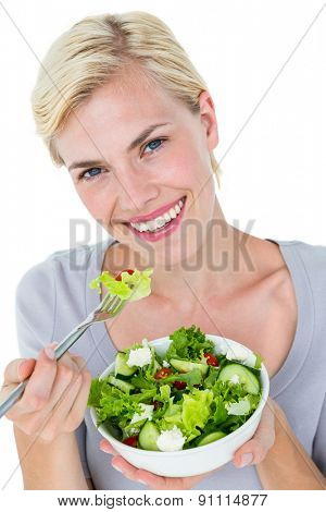 Happy blonde woman holding bowl of salad on white background