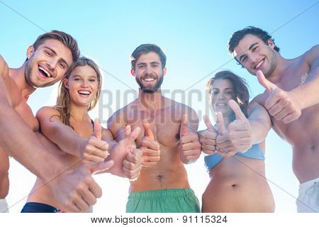 Happy friends smiling at camera showing thumbs up at the beach