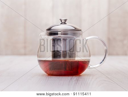 the glass teapot tea, on woodwn table