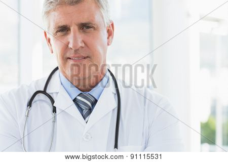 Confident male doctor looking at camera in medical office
