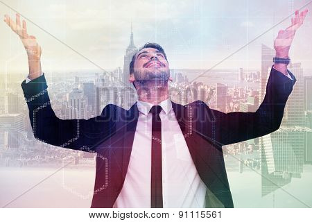 Businessman cheering with hands raised against server room with towers