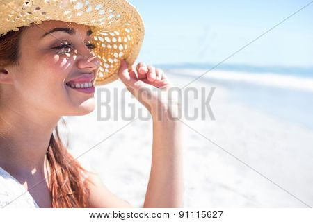 Brunette sitting in the sand and looking at the sea at the beach