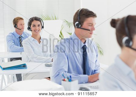 Business team working on computers and wearing headsets in call center