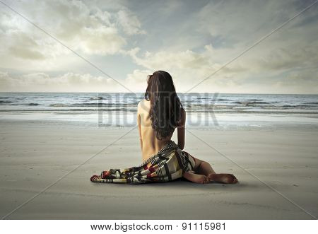 Naked woman sitting on the sand