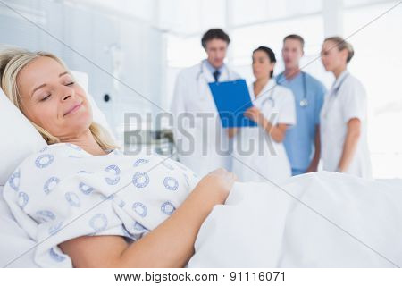Sleeping patient with doctors behind in hospital room