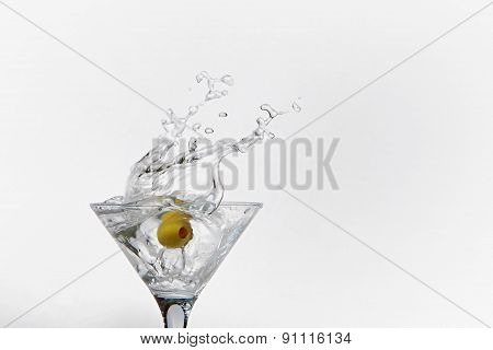 Splash from olive in a glass of cocktail
