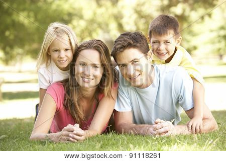 Young Family Relaxing Together In Park
